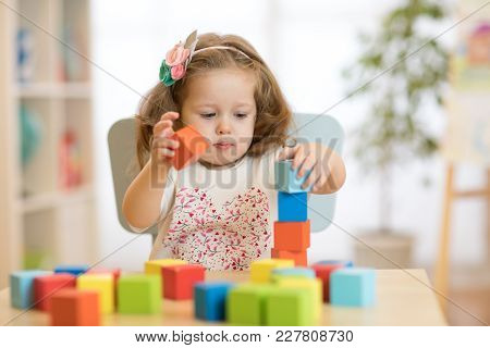 Cute Child Playing With Block Toys In Day Care Center
