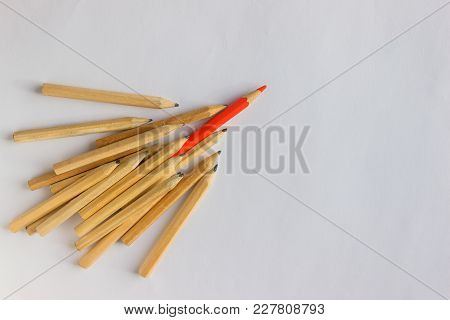 Red Pencil Standing Out From Crowd Of Plenty Identical  Pencils On Table. Leadership, Uniqueness, In