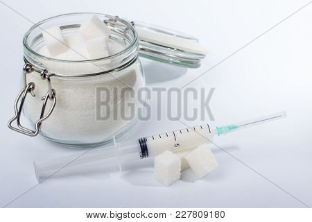 The Syringe And Glass Jar With Sugar On A White Background