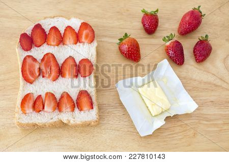 Whole Wheat Bread And Pieces Of Strawberry And Fresh Butter Piece On Wooden Cutting Board.