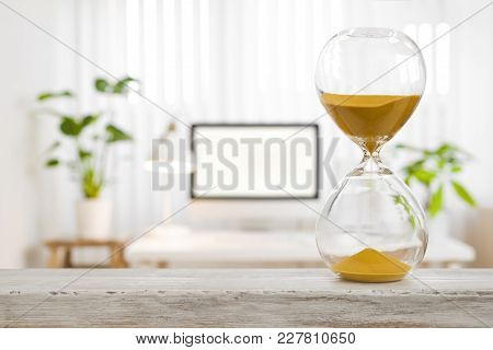 Hourglass Business Concept. Sand Glass In Front Of Blurred Office