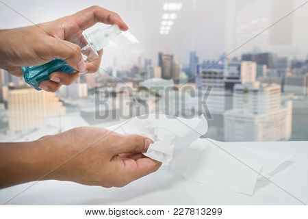 Close Up Man Hand Use Alcohol Bottle With Tissue Paper For Sanitary In Office