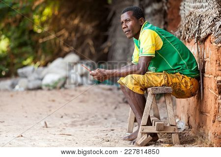 Stone Town, Zanzibar - January 20, 2015: Man Sitting On Wooden Bench Looking To The Distance