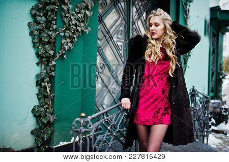 Elegance Blonde Girl In Red Evening Dress And Fur Coat At Streets Of City.