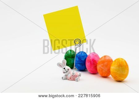 Easter Composition With Colored Eggs And A Bunny Holding Paper For A Message
