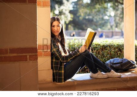 Smiley Young Girl Sitting On The Window At The University Terrace With A Book In Her Hands