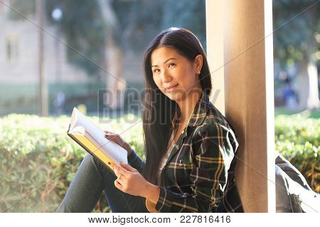 Pretty Young Asian Girl Smiles And Looks In The Camera, Holding A Book In Her Hands