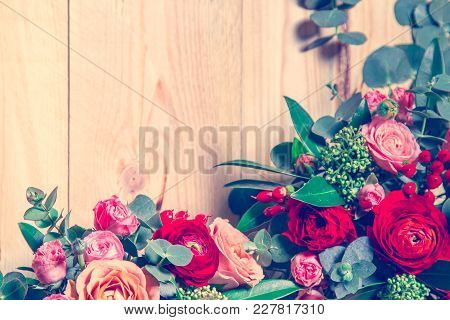 Wooden Background With Flowers At The Edges. Next To Free Space For Inscription