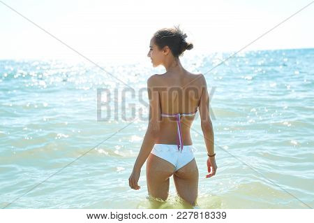 Beautiful Sexual Young Woman In White Bikini Stands On The Beach Against The Sea And Sky At Sunny Da