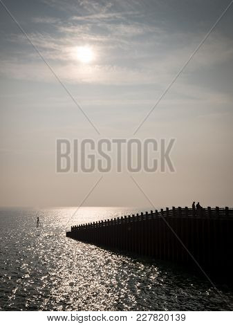 Calm Sea With People And Pier Silhouettes; South Coast, England