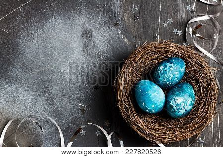 Easter Eggs In Nest Painted By Hand In Blue Color On Dark Background With Copyspace. Chicken And Qua
