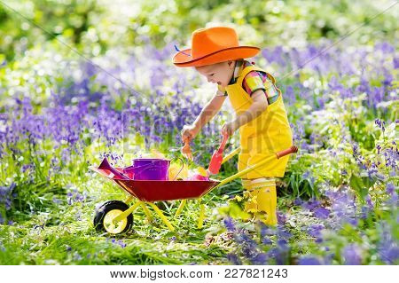 Kids In Bluebell Woodland. Child With Flowers, Garden Tools And Wheelbarrow. Boy Gardening. Children