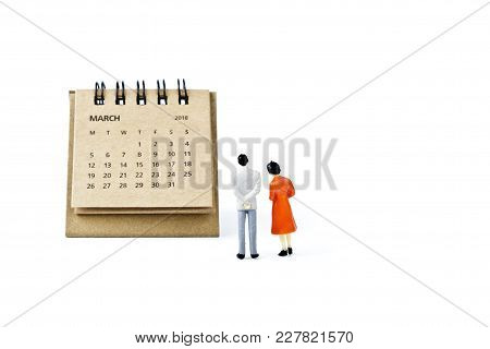 March. Two Thousand Eighteen Year Calendar And Two Miniature Plastic Figures. Man And Woman On White