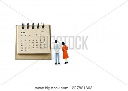 July. Two Thousand Eighteen Year Calendar And Two Miniature Plastic Figures. Man And Woman On White