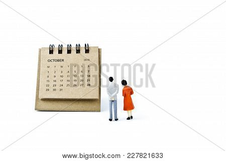 October. Two Thousand Eighteen Year Calendar And Two Miniature Plastic Figures. Man And Woman On Whi