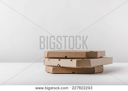 View Of Three Pizza Boxes On White Tabletop