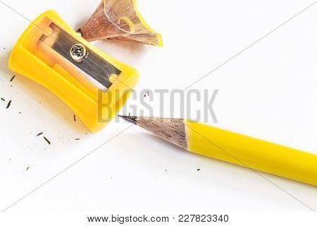 Pencil-sharpener And Pencil Isolated On White Paper Background.  With Copy Space For Your Text.