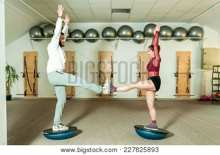 Young Beautiful And Attractive Fitness Couple Workout On Thair Balance By Standing On The Half Ball