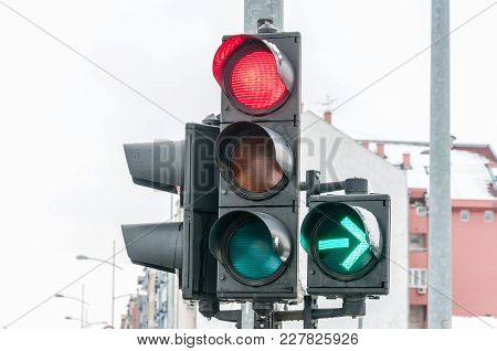 Close Up Of Traffic Light On The Crossroad With Red Light For Straight Direction But Green Arrow For