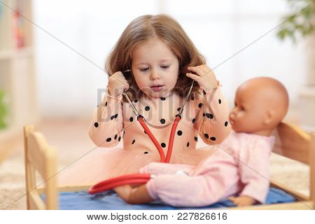 Two Years Old Girl Playing Doctor With Doll In Nursery Or Daycare