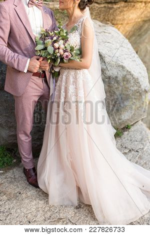 Wedding. The Girl In A Beige Dress And A Guy In A Suit Are Holding A Beautiful Bouquet Of White, Pur