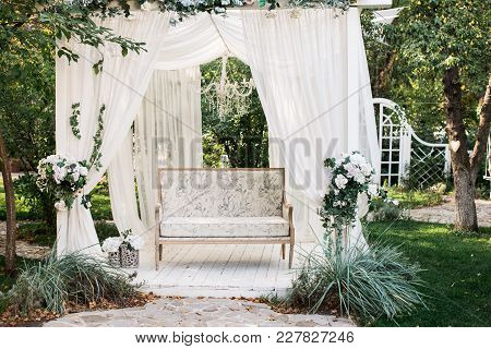 In The Garden There Is A Podium On Which A Beautiful White Sofa In The Style Of Provence Or Rustic.