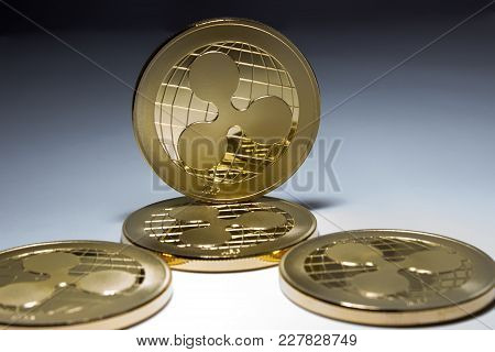On A Black And White Background Are Gold Coins Of A Digital Crypto  Currency - Ripple. In Addition T