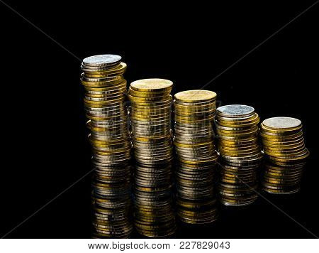 Macro Shot Detail Of Golden And Silver Color Coin Stacks On Dark Background With Copy Space For Text