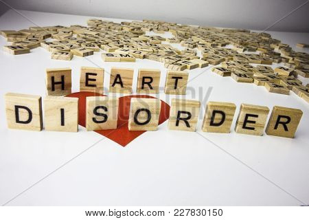 Word Heart Disorder. Wooden Letters Spelling The Phrase Heart Disorder On White Background. One Red