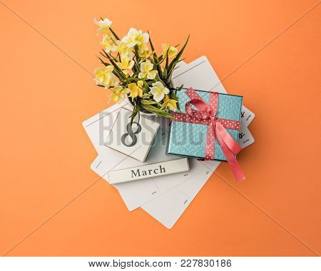 The Top View Of Orange Desk With Gift, Flowers And Notebook