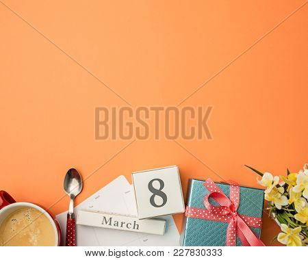 The Top View Of Orange Desk With Cup Of Coffee, Gift, Flowers And Notebook
