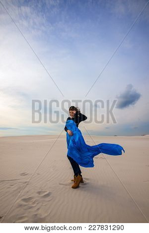Romantic Girl, Wearing In A Flying Blue Scarf, Is Walking In The Desert - On The Beginning Of Storm.