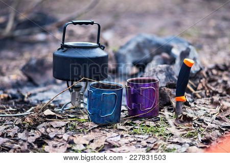 Camp In A Spring Forest - Small Steel Kettle Stands On Gas Burner Next To Knife And Two Cup On The L