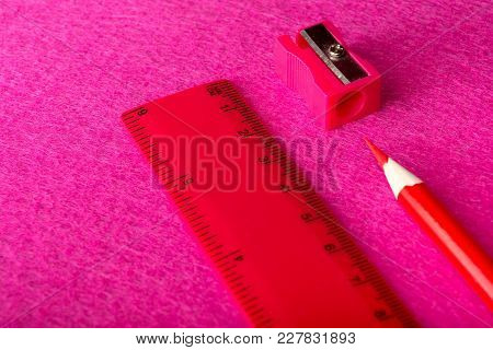 Red Pencil With Pencil Sharpener And Ruler On Red Background. Stationery. Office Tool.