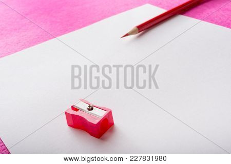 Red Pencil Sharpener Close-up And Red Pencil On White Paper Sheet. Stationery. Office Tool.