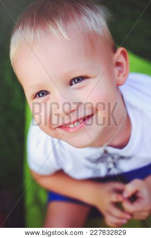 Happy Blue-eyed Blond Boy Looking Up At Camera Smiling. Soft Warm Toning