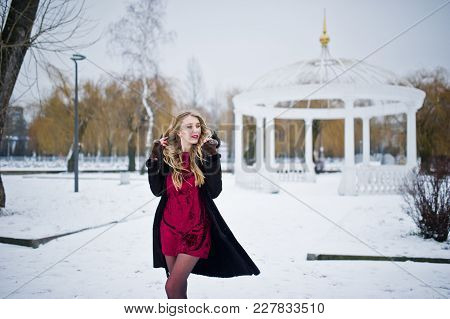 Elegance Blonde Girl In Fur Coat And Red Evening Dress Posed At Winter Snowy Day.