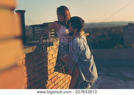 Couple In Love Having Fun On A Building Rooftop, Enjoying A Beautiful Summer Sunset Over The City; G
