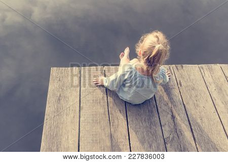 Lonely Small Girl Dreaming On Dock Near River. Riskily Situation