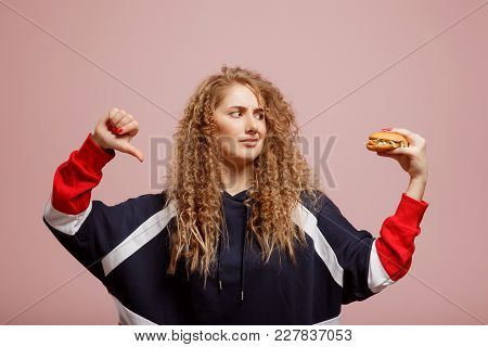 American Beautiful Girl Shows Thumbs Up Slash Dumb Hamburger Harmful And Fatty Food. Concept Rejecti