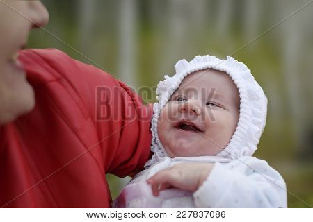 Laughing Baby. A Moment Of Joy Between A Mother And Suckling, A Woman Holding Up A Baby