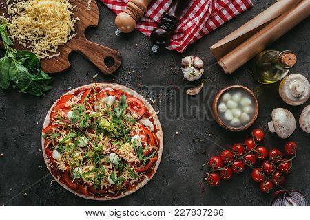 Top View Of Unprepared Pizza With Ingredients On Concrete Table