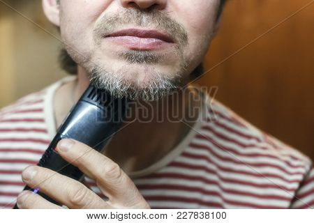 A Middle-aged Bearded Man Shaves Trimmer. Close-up