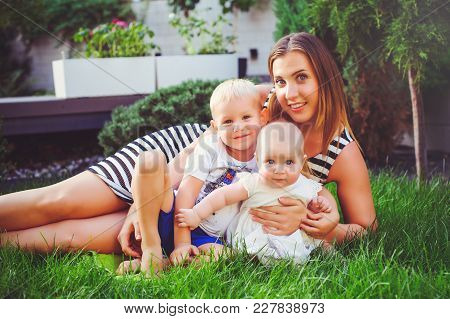 Woman Mother With Two Young Children Lie On A Green Lawn, Concept Maternity And Parenting