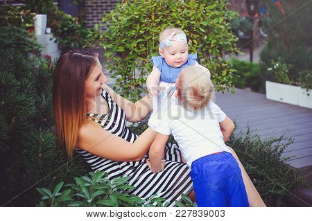 Woman Mother With Two Young Children Lie On A Green Lawn, Entertain The Girl, The Concept Of Motherh