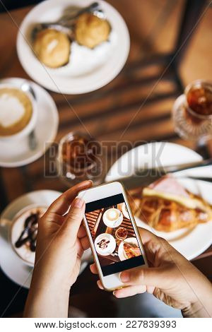 Food Blogger With Telephone. Breakfast For Two: Croissant With Ham, Coffee, Refreshing Drink, Eclair