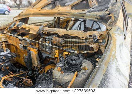 Inside Of A Burnt Out Car Showing Metal Remains Of A Steering Wheel With Foam Pieces.