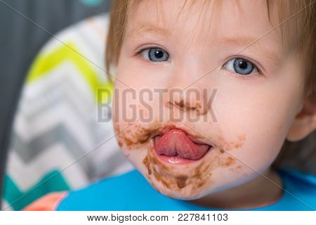 A Toddler Sticking Out Her Tongue After Eating Some Chocolate