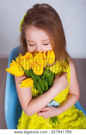 Beautiful Little Girl Smelling The Aroma Of Bouquet Of Fresh Tulips. Spring And Summer Portrait Of C