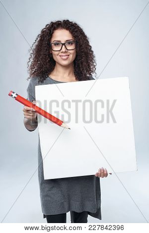 Beautiful Curly Female In Eyeglasses Holding Blank Whiteboard And Pointing At It With Big Red Pencil